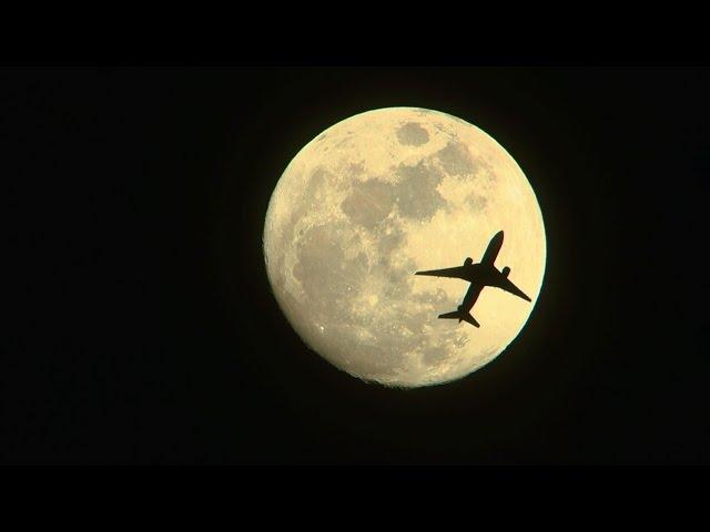 満月間近の月を横切る飛行機