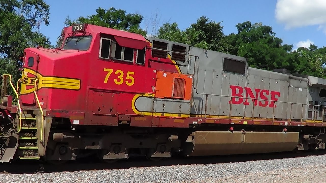 Car Drives Past Gates In Front Of Bnsf Freight With Warbonnet Youtube