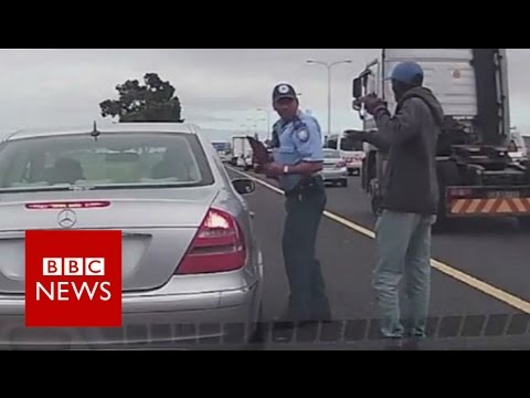 Policeman shot in the back, still issues ticket - BBC News