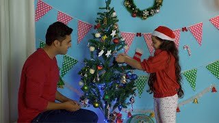 Young beautiful girl hanging colorful balls on a Christmas tree with her Dad
