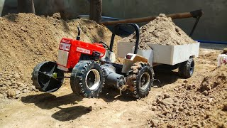 Toy tractor pulling full loaded trolley in sand