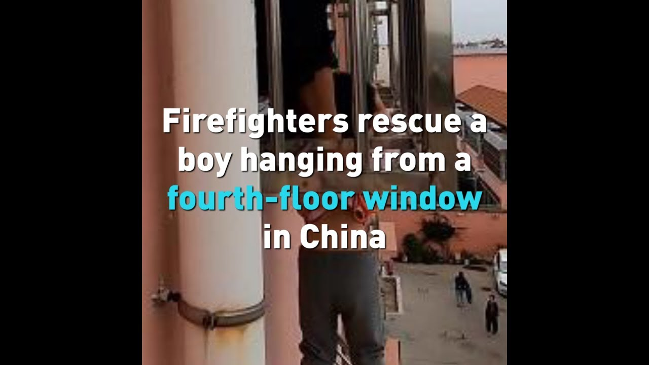 Firefighters rescue a boy hanging from
