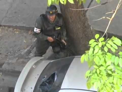 Venezuelan National Guard shooting at people in buildings during riots in Venezuela.