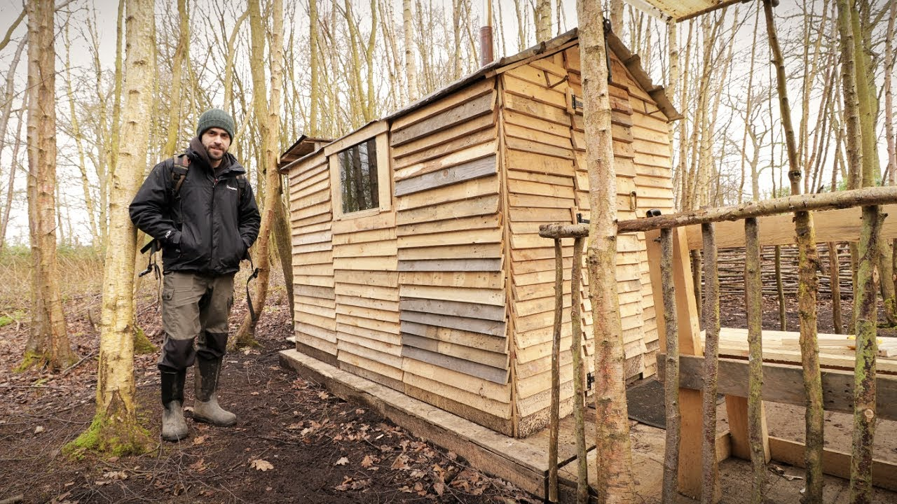 Off grid pallet wood cabin picket fence build woodstove for How to build a cabin floor