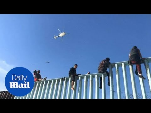 First members of migrant caravan arrive and climb border wall
