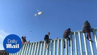 First members of migrant caravan arrive and climb border wall