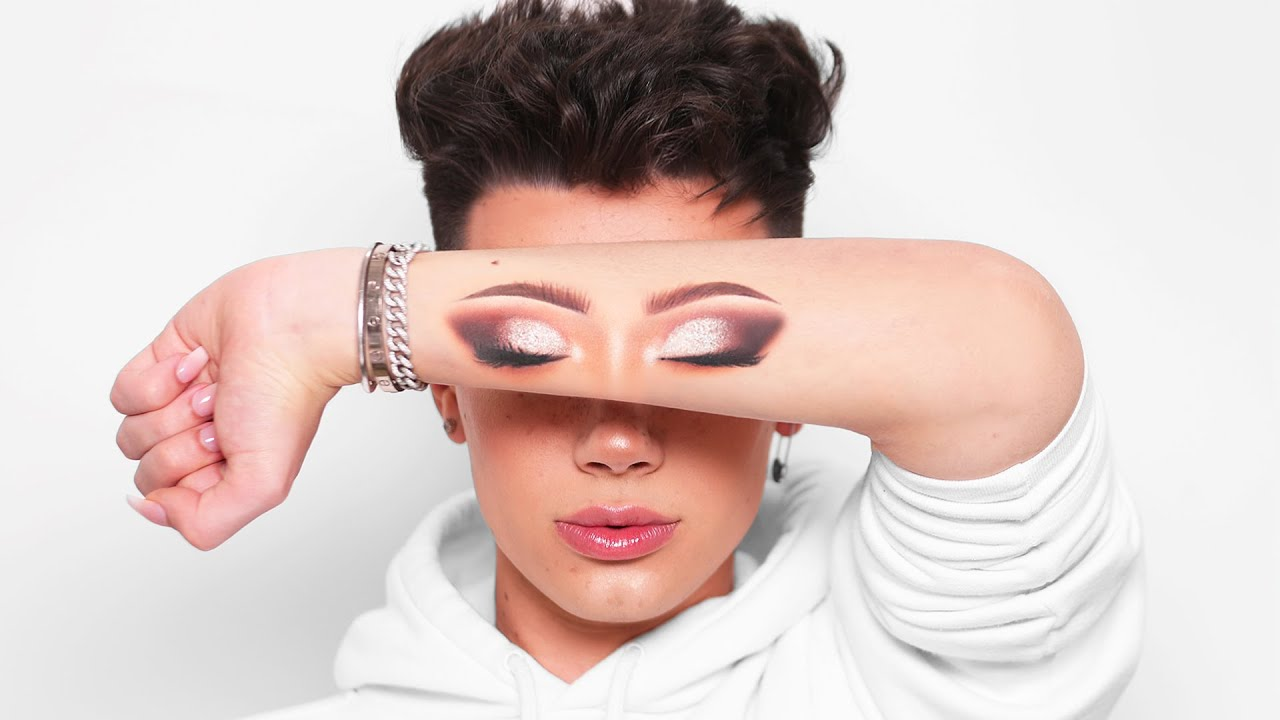 James Charles holding up eye makeup on his arm