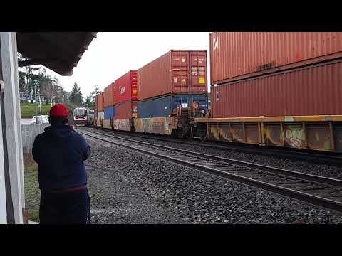northbound up freight train going slow while a speedy amtrak passes by