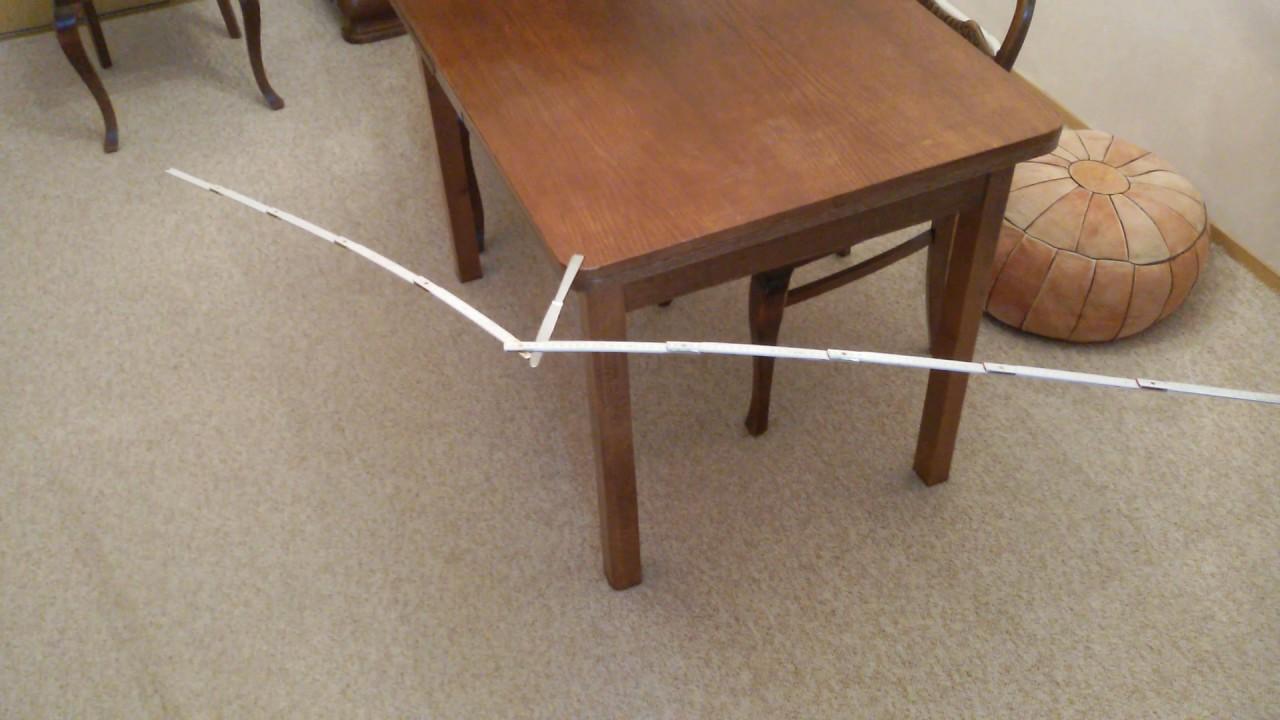 schwebender zollstock auf messerspitze, die auf tischkante
