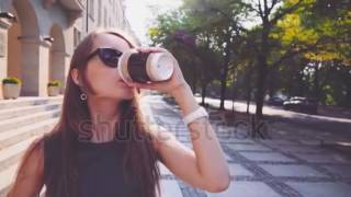 stock footage attractive business woman with digital tablet walking in the city and drinking coffee