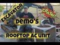 Excavator removes big rooftop ac unit