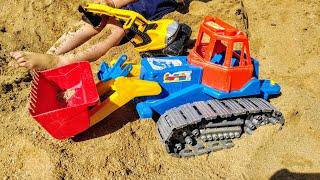 Малыш играет в песочнице с тракторами, ищет игрушку. Видео для детей.