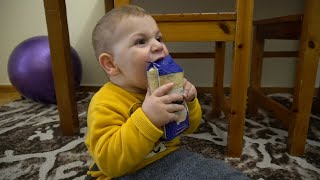 Baby boy tries to open a packet of rice