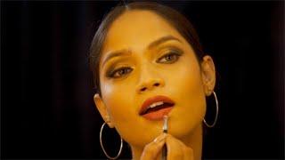 Stunning Indian ramp model applying light shade lip color using a brush - Black background