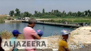 Mosul refugees return home through new bridge after conflict