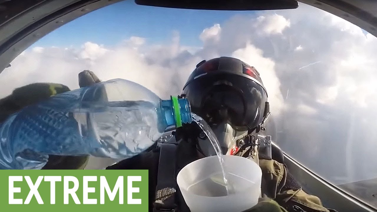 Fighter jet pilot drinks water cup while flying upside down