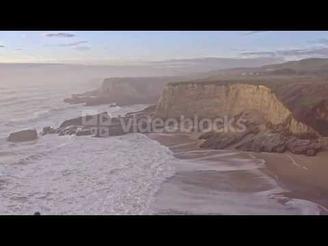aerial of man standing over cliff looking down at ocean coastline nw1 ibtql