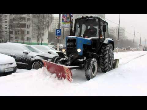Трактор чистит тротуар. The tractor cleans the sidewalk.