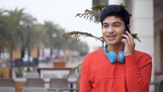 Cute Indian boy happily talking to his friend over a phone call - technology concept