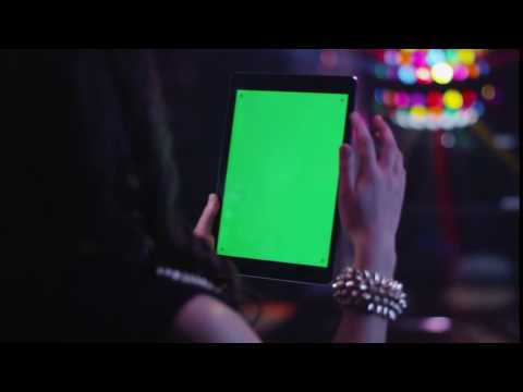 Teen girl is holding tablet pc with green screen in portrait mode