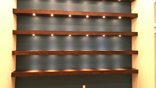 Build wall-to-wall shelves with recessed lights