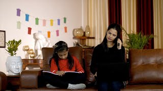 Cute little kid studying and her mom is doing office work at home - Indian family