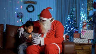 Happy Santa and cute boy opening a special gift together during Christmas time