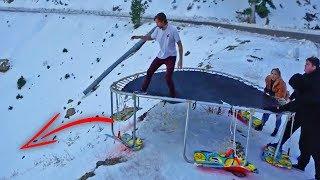 Snowboarding 15ft trampoline down HUGE hill! (flips)