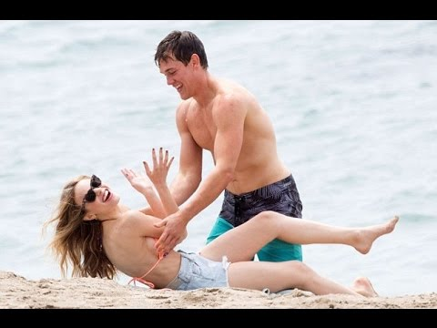 Halston Sage frolics on the beach with Taylor John Smith before they indulge in a steamy smooch