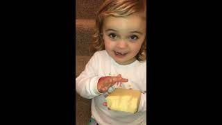Little girl loves eating a big block of cheese