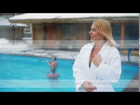 Young blonde woman in bathrobe near outdoor swimming pool at winter