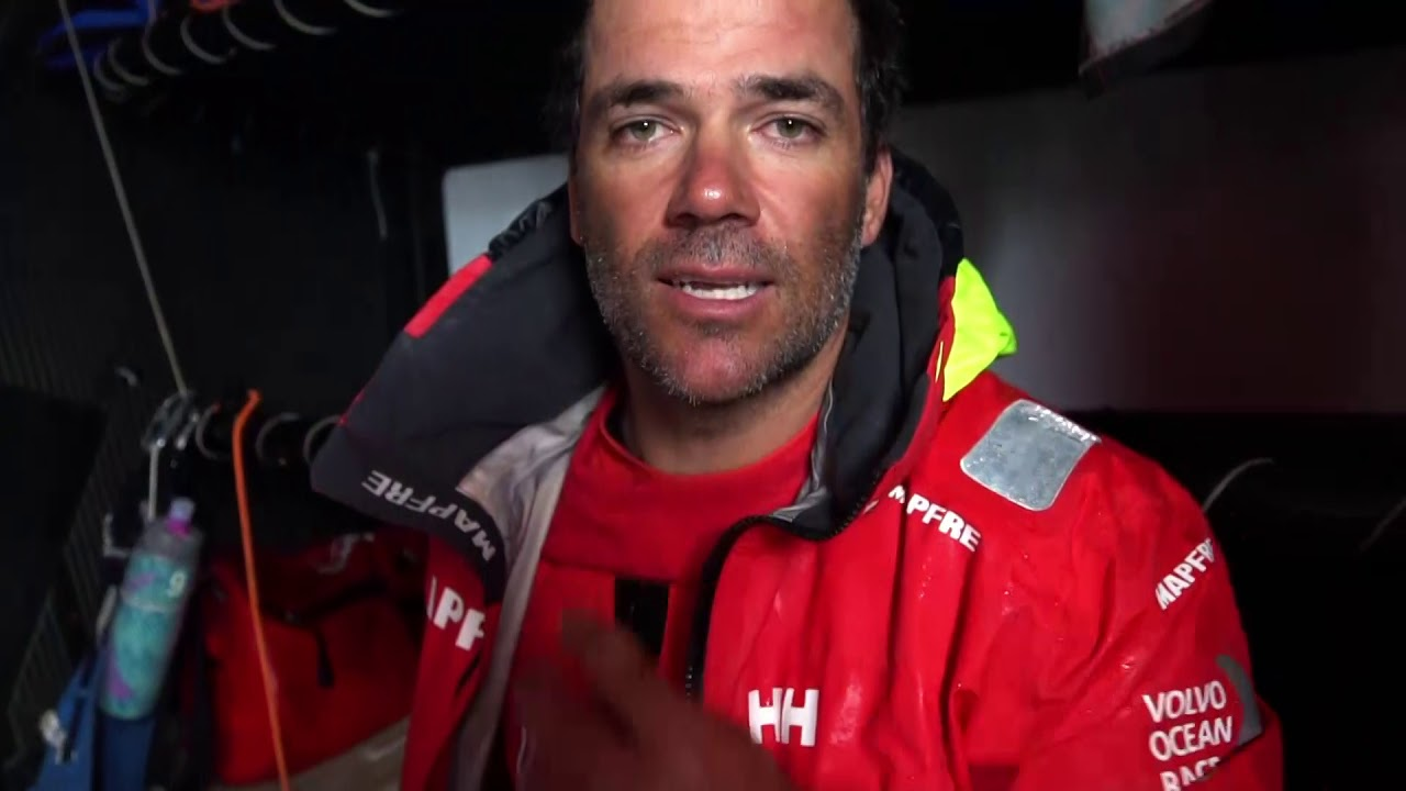 """Xabi and Joan talk at nav station. Neti, on deck, reads out latest sched. """"MAPFRE (us): third."""" Rob, on the helm as they sail in fog in light winds: Last sched sounds pretty good. Talks about the strategy getting through the front and timing their tack right. We were hoping just to get to fourth. Now we're up to third and Dongfeng isn't that far away. Got 200 miles to go. Gotta keep fighting. Blair, forward, clears a halyard. Crew working in the cockpit. Slomo grinding. Sail change. Pablo on the helm. Rob, gesturing to port: """"Brunel's down here 17 miles."""" Pablo, below: The last sched was better than we hoped. He talks about the boats ahead. Will be very tricky at the arrival in Newport, light wind and current. Anything can happen. So go MAPFRE... The weather forecast opened a gate for us. It was a tough night, but we sailed very good, so we softened up some miles to the leaders, and then the compression was very good to us. Neti, on deck, talks in Spanish about thier change of fortune. """"Vamos MAPFRE. Vamos MAPFRE."""" Crash cam footage from the night before of them broaching. Spreader cam view of the cockpit. Sail change on the foredeck: Hanking on the J1. Hoisting the J1 inside the J0."""