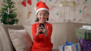 Happy girl sitting on a couch watching a cartoon on her smartphone  - Christmas Theme with Tree and Gifts