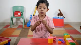 Shot of a cute Indian child making shapes from clay dough