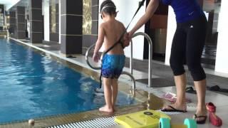 Марат с тренером учится плавать в бассейне Kid swimtraining in swimming pool