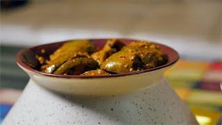 Pan shot of ready mango pickles / achar kept in the ceramic pot