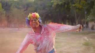Young happy man having fun during joyful Holi celebration - Indian festival and culture