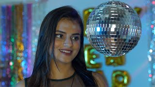 Pretty Indian female gives a charming toothy smile to the camera while standing near a disco ball