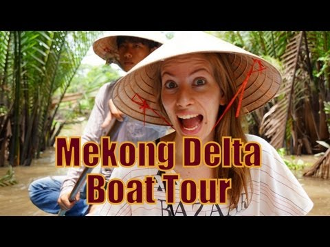 Paddling down the Mekong Delta River on a rowboat tour while wearing our conical hats in Vietnam