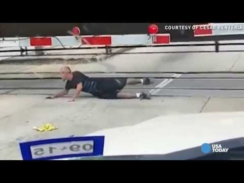 Man rolls under moving train in heart-stopping video