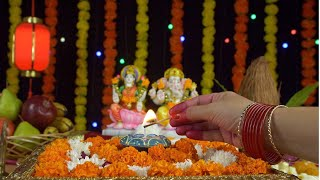 Shot of an Indian female's hand lighting up a Diya in front of Ganesh Ji and Laxmi Ji - Diwali festival