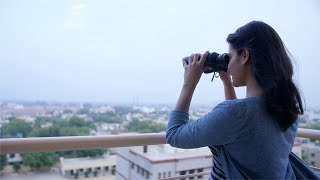 Shot of an Indian girl standing in her house balcony and glancing through binoculars