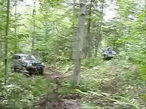 2 jeeps going trying to make it up a trail