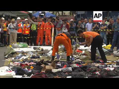 Search teams check clothing collected at sea  at Jakarta's port