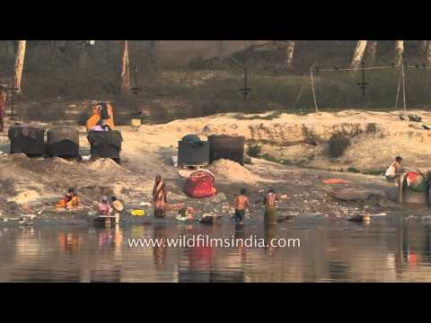 People bathe and wash clothes in polluted river Yamuna