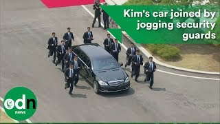 Kim Jong-Un's car surrounded by jogging security guards