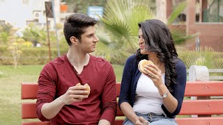 Couple sitting on a bench outdoor eating a yummy burger