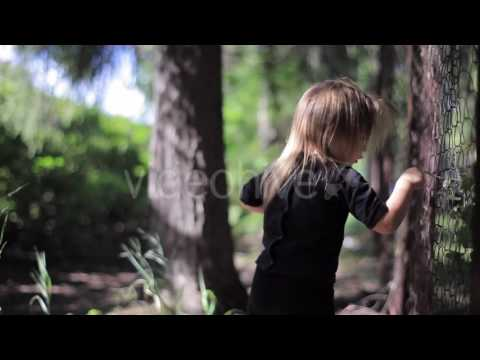 Little Girl in a Black Shirt and Pants Stands at the Grid and Tearing Leaves Over it