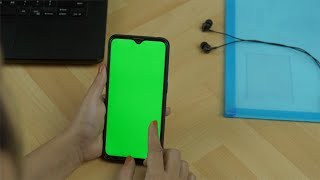 Overhead shot of an Indian female using her green mock-up screen smartphone