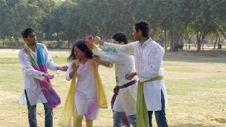 Young boys inappropriately coloring a woman with powder colors at a Holi party